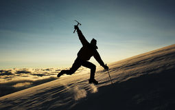 Jumping man on a snowy slope in the mountains Stock Images