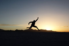 Jumping man at sunset. Silhouette of jumping man at sunset royalty free stock photo