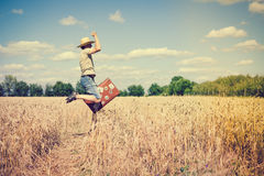 Jumping man wearing straw hat with suitcase in. Happy jumping man wearing straw hat with valize in wheat field. He rising hand and having fun over blue sky Royalty Free Stock Images