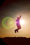Jumping man. Young crazy  man is jumping on colorful sky background.Silhouette of jumping man and beautiful sunset sky. Stock Images