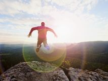 Jumping man. Young crazy man is jumping on  rocky summit above landscape. Silhouette of jumping man Stock Photo