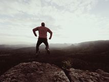 Jumping man. Young crazy man is jumping on  rocky summit above landscape. Silhouette of jumping man Royalty Free Stock Images