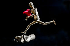 Jumping mannequin. Wooden mannequin holding a heart and jumping over a wooden hand Stock Photos