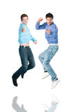 Jumping men pointing at you. Two young happy jumping men pointing at you with index finger Royalty Free Stock Photos