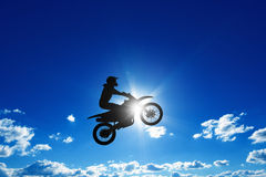 Jumping motorcycle rider. Active sports background - jumping motorcycle rider silhouette, blue sky, bright sun Royalty Free Stock Image