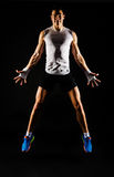 Jumping muscular man. Jumping muscular smiling young man with fit body Royalty Free Stock Image