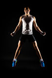 Jumping muscular man. Jumping muscular young man with fit body Stock Photography