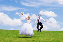 Jumping newly-married couple royalty free stock photography