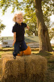 Jumping off a hay bale. Young Boy jumping off of a hay bale at a pumpkin patch Royalty Free Stock Photo