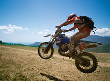 Jumping off-road rider. Off-road rider is jumping against a summer mountains Royalty Free Stock Photo