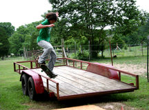 Jumping onto Rail. Teen male skateboarder jumping onto trailer rail. Shot with Canon 20D Royalty Free Stock Image
