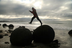Jumping over boulders Stock Image
