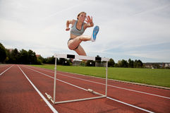 Jumping over a hurdle. A young athlete jumping over a hurdle Stock Photo