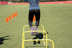 Jumping over hurdles during practice Stock Photography