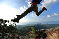 Jumping over precipice between two rocky mountains . freedom Royalty Free Stock Photography