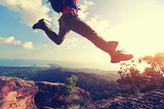 Jumping over precipice between two rocky mountains at sunset Royalty Free Stock Images