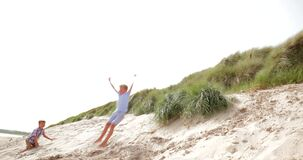 Jumping Over the Sand Dunes. Slow motion, side view, of a little boy jumping over a sand dune stock video footage
