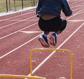 Jumping over two feet high yellow hurdles Stock Images