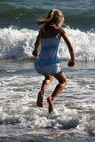 Jumping over the waves. Girl jumping over the waves royalty free stock image