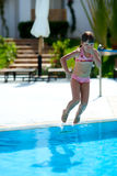 Jumping in pool. Girl jumping in pool summer holiday Royalty Free Stock Photography