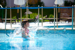 Jumping in pool. Girl jumping in pool holiday Royalty Free Stock Photo