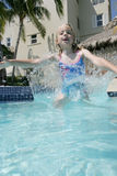 Jumping in Pool. A little girl jumping in the swimming pool of her hotel Stock Image