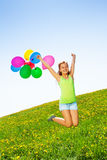 Jumping positive girl with balloons in summer Royalty Free Stock Photo
