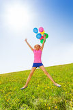 Jumping positive girl with balloons in summer Royalty Free Stock Photography