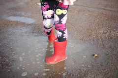 Jumping in puddles. A child wearing red rubber boots jumping in muddy puddles and having fun royalty free stock photography