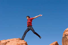 Jumping on red rocks Royalty Free Stock Photo