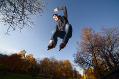 Jumping Roller-skater. Wide-angle shot of a jumping roller-skater on a blue sky background Royalty Free Stock Photos
