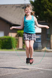 Jumping Rope. Young girl jumping rope outdoors Royalty Free Stock Photos