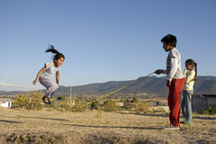 Jumping the rope. Three children playing to jump rope at a rural area of Mexico Stock Images