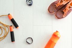 Jumping rope, timer, plastic bottle and sneakers. On wooden background, top view Stock Photos