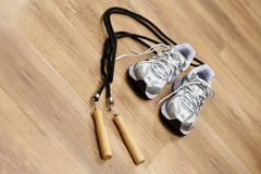 Jumping rope and trainers. On gym floor Stock Photo