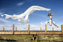 Jumping with a scarf. Young beautiful woman jumping with a scarf in a beautiful day Royalty Free Stock Photography