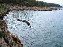 Jumping in sea. Young man jumps in the sea water Royalty Free Stock Photography