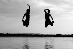 Jumping Silhouette. Two people jump into the water of a swimming pool with the sun behind them Royalty Free Stock Image