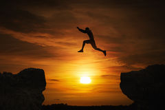 Jumping. Silhouette of a man jumping over abyss at sunset with copy space stock photos