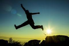 Jumping silhouette. Silhouette of man jumping on top Stock Images