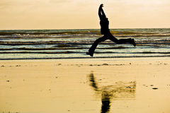 Jumping Silhouette by the Sea Shore. The ambiguous silhouette of a person who is jumping by the shore of the pacific ocean at sunset Stock Photography