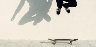 Jumping On Skateboard. Man jumping on the skateboard on the city street Royalty Free Stock Photos
