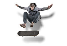 Jumping skateboarder isolated. Skateboarder making trick in the air with shadow behind isolated on white background stock image