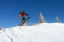 Jumping skier. Male skier jumping on a mountain slope against blue sky Stock Image