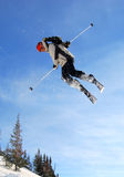 Jumping skier. Young freestyle male skier jumping and rotating in stunt high in the air Stock Photo