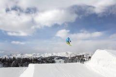 Jumping skier. At jump inhigh mountains at sunny day Royalty Free Stock Image