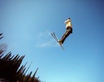 Jumping skier. At jump inhigh mountains at sunny day Royalty Free Stock Photos