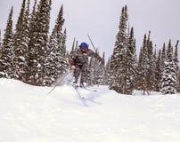 Jumping skier. At jump inhigh mountains at sunny day Stock Image