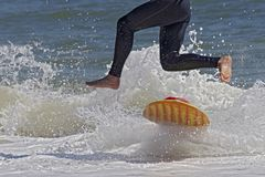 Jumping Skimboarder. Skimboarder in wetsuit leaping from board Stock Photos