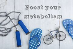 Jumping/skipping rope with blue handles, flip flops, model of bicycle on white wooden background with text boost your metabolism. Fitness/sport and healthy stock image